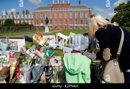 London, UK. 31st Aug, 2017. A boy and his mother look at the tributes of flowers and cards at the Gate of Kensington - Stock Photo