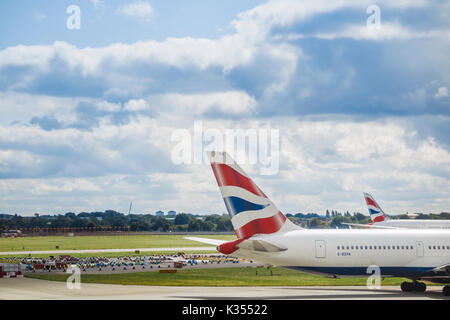 Tail fin with British Airways colours on a passenger aircraft parked in London Heathrow Airport Terminal 3 - Stock Photo