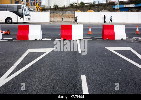 Red and white concrete blocks on a road junction blocking a street - Stock Photo