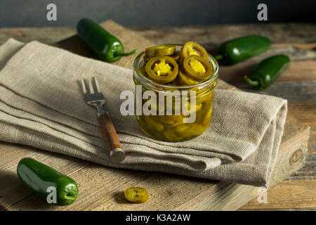 Green Organic Pickled Jalapenos in a Jar - Stock Photo