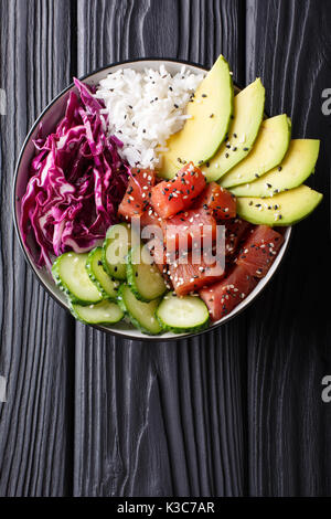 Raw Organic Ahi Tuna Poke Bowl with Rice and Veggies close-up on the table. Top view from above vertical - Stock Photo