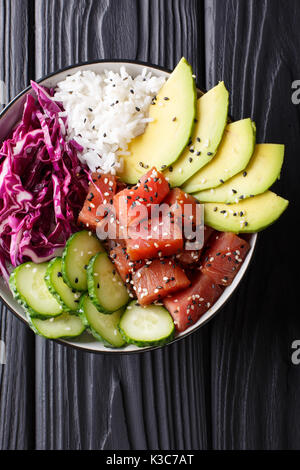 Hawaiian tuna poke bowl with avocado, red cabbage, cucumber and sesame seeds on black wooden background. Top view - Stock Photo