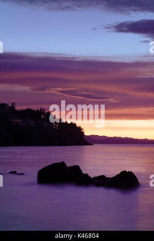 Beautiful pink sunset scenery on the ocean coast with lights of residential houses on dark rocky shores in Nanaimo, - Stock Photo