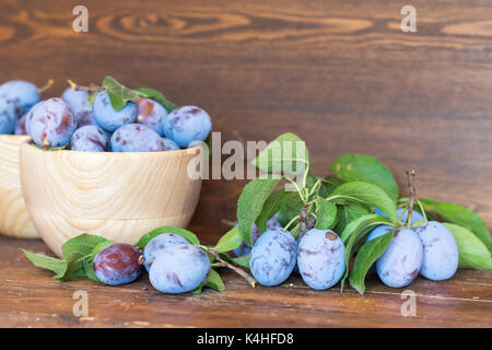 Fresh plums with green leaves in wooden pot on the dark wooden table. Shallow depth of field. Toned. - Stock Photo