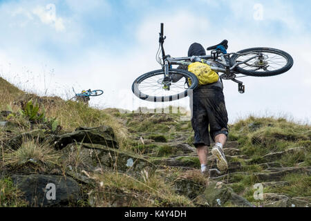 Mountain biker: Cyclist carrying a mountain bike up a hill. Jacob's Ladder, Derbyshire, England, UK - Stock Photo