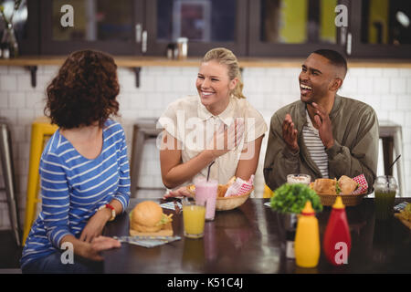 Cheerful young friends talking while sitting with food and drink at table in coffee shop - Stock Photo