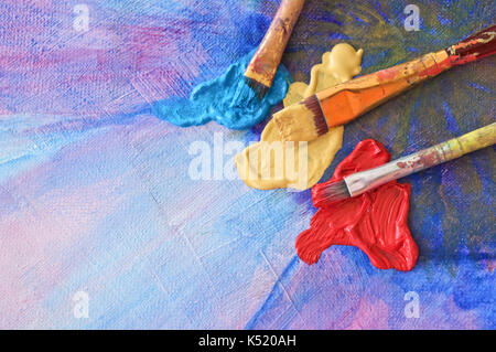 Brushes and colors on painted canvas - Stock Photo