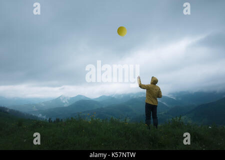 Man with yellow balloon in higt mountains - Stock Photo