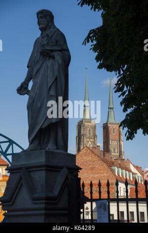 St. John the Baptist figure, Most Tumski (Tumski Bridge) and Gothic Archikatedra Sw. Jana Chrzciciela (Cathedral - Stock Photo