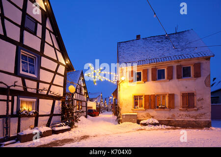 An alley with half-timbered houses and christmas lights at night during snowfall in Lachen, Neustadt an der Weinstrasse, - Stock Photo