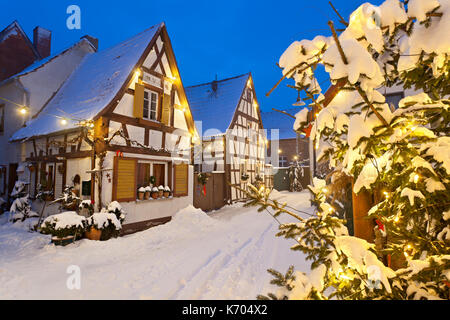 An old village street with half-timbered houses and christmas lights at night during snowfall in Lachen, Neustadt - Stock Photo