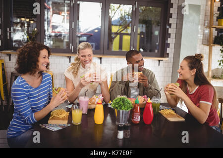 Smiling young friends eating food while sitting at table in coffee shop - Stock Photo