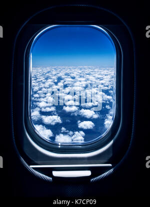 Beautiful white fluffy clouds seen through the airplane window, aerial view, air travel concept - Stock Photo