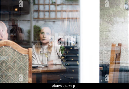 Old adult friends having meeting in pub. Shot through window with reflections on glass. Horizontal orientation - Stock Photo