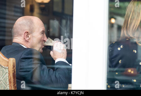 Senior man with friends in pub drink porter type beer. Shot through window with reflections on glass. Horizontal - Stock Photo