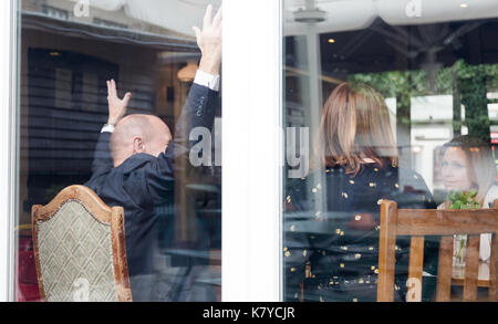 Senior man with hands up whille enjoy friends meeting in pub. Horizontal close up shot through window with reflection - Stock Photo