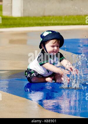 Baby boy, sitting, wearing cute swim suit, t-shirt and hat, playing with spraying water at park. Florida, USA. - Stock Photo
