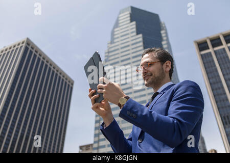 Smiling young businessman looking at digital tablet by New York skyscrapers, USA - Stock Photo