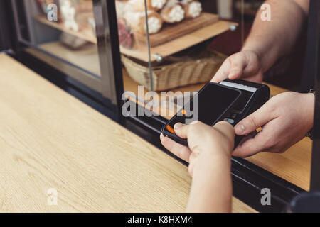Person paying pay through smartphone using NFC - Stock Photo