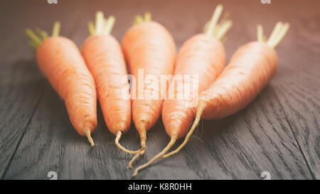 fresh carrots on old oak table - Stock Photo