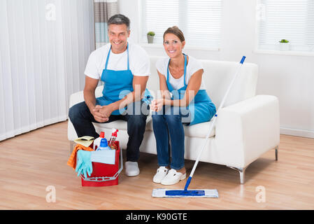 Two Happy Cleaners Sitting On Couch In Living Room - Stock Photo