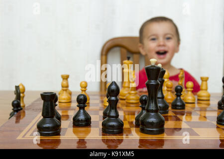Cute toddler boy playing chess - Stock Photo