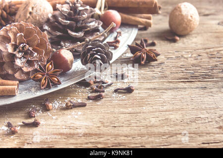 Christmas vintage decoration with cinnamon sticks and star anise, cones, nuts and Christmas ornaments over rustic - Stock Photo