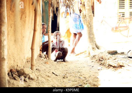 Indian village children sitting house exterior looking at camera - Stock Photo
