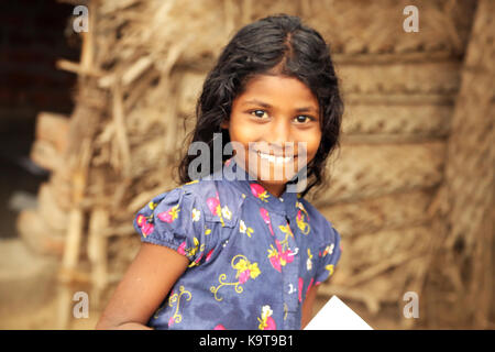 Unidentified Happy Indian rural girl smiling at camera - Stock Photo