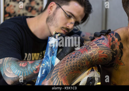 London, UK. 24th September 2017. A tattoo artist works on a man's tattoo at the London Tattoo Convention 2017 held - Stock Photo