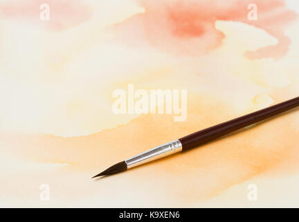 Painting tools on abstract watercolor painting - Stock Photo