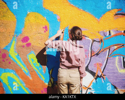 Beautiful Young Girl making a colorful graffiti with aerosol spray on urban street wall. Cinematic toned shot. Creative - Stock Photo