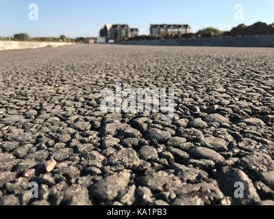 Rough asphalt pavement in the summer season - Stock Photo