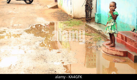 Happy Indian rural child girl front of their house - Stock Photo