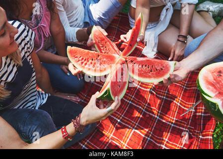 Cheerful friends enjoying watermelon on picnic on sunny summer day - Stock Photo