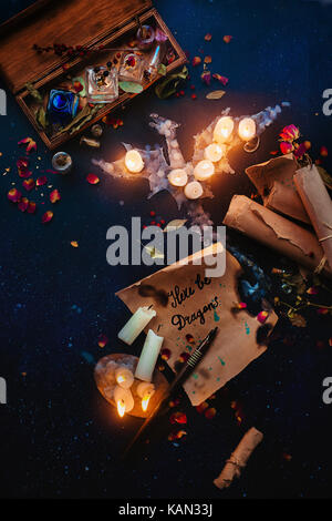 Fantasy still life with a dragon made of candle flame, spell scrolls, herbs, potion bottles and rose petals. Witch - Stock Photo