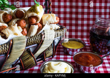 Wicker basket with mini artisan hot dogs (Sausage in the dough) with mustard, mayonnaise and cola on a plaid background - Stock Photo