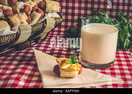 Wicker basket with artisan mini hot dogs (Sausage in the dough) with sausage on a napkin covered in mustard, mayonnaise - Stock Photo
