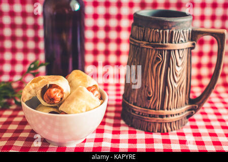Plate Mini hot dogs homemade (sausage in pastry) on napkin with a bottle of dark beer and earthenware mug on a plaid - Stock Photo