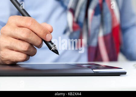 Hand of graphic designer on graphics tablet - Stock Photo