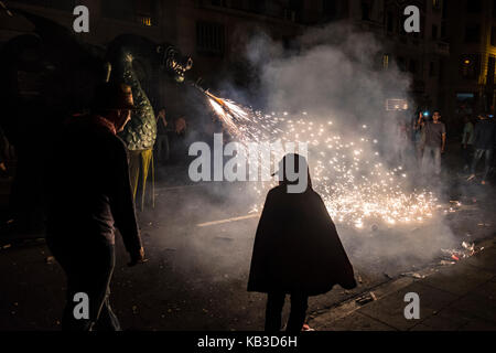 Correfocs are among the most striking features present in Catalan festivals. In the correfoc, a group of individuals - Stock Photo