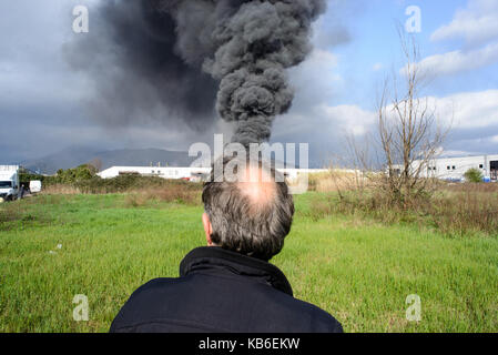 An elderly man seen from behind with a cloud of smoke on the background coming out of his head, Prato Italy - Stock Photo