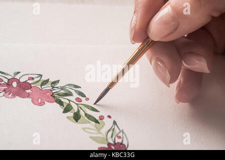 Close up of artist with brush painting flower frame with acrylic paint on paper. Copy space for logo, advertisement - Stock Photo