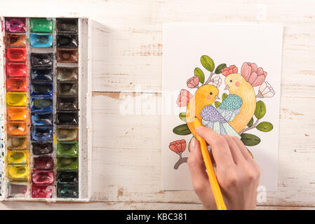 Top view of artist painting beautiful design picture of birds with markers on paper - Stock Photo
