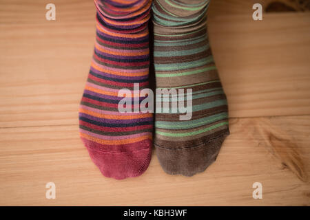 Womans feet wearing multicolored socks at home - Stock Photo