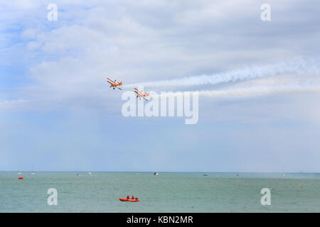 Breitling Wingwalkers aerobatics and wingwalking team  over the sea, part of Airbourne, Eastbourne Air show 2017, - Stock Photo