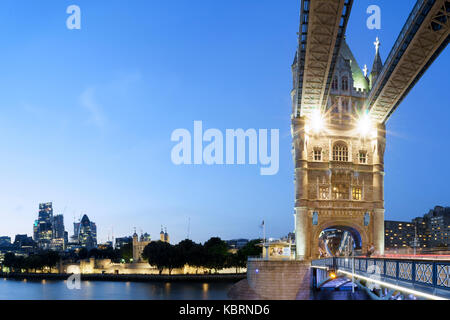 UK, London, Tower Bridge and the city skyline along River Thames with view of Tower of London, lit up at dusk - Stock Photo