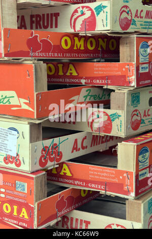 Fresh fruit market packaging and crates stacked up in a regular repeating pattern and very colourful boxes and cartons - Stock Photo