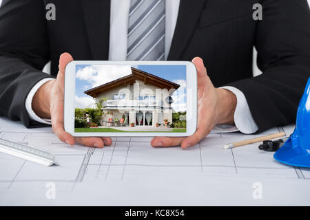 Close-up Of Young Male Architect Showing House On Digital Tablet Over Blueprint In Office - Stock Photo