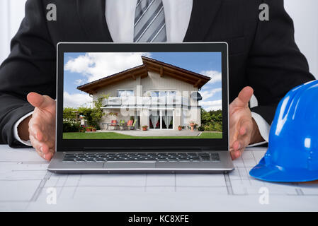 Close-up Of An Architect Showing His Laptop Over Blue Print In Office - Stock Photo